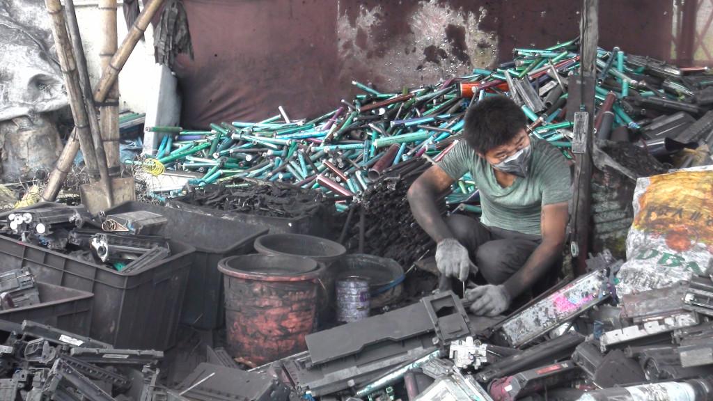 Laborer dismantling toner cartridges. Guiyu, China