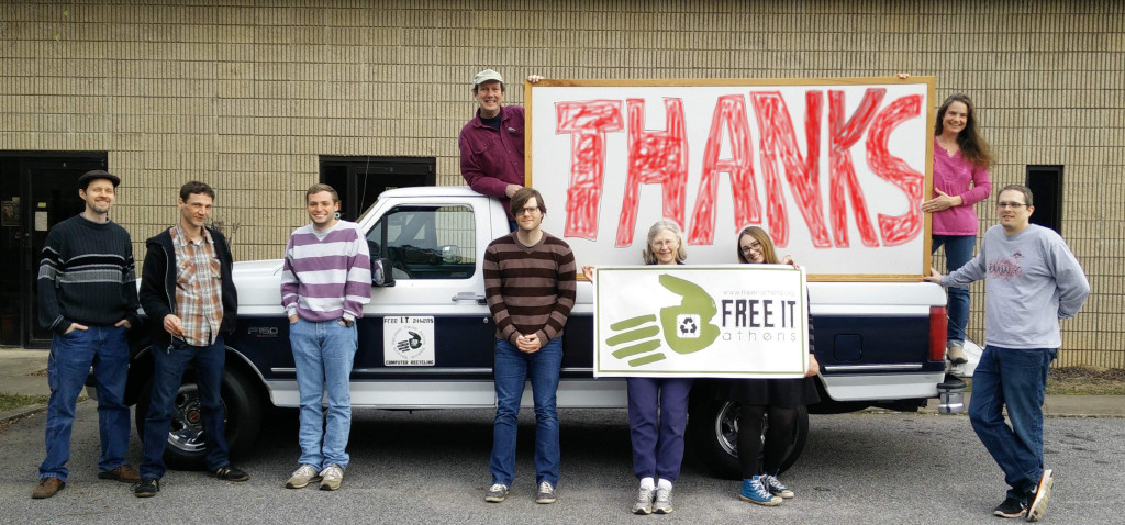 """a group of volunteers stand with a sign that says """"Thanks"""""""
