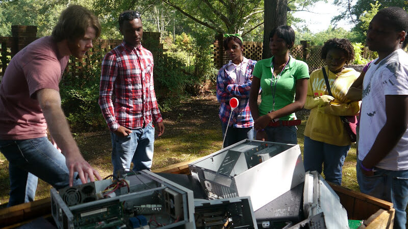a group of volunteers around a Gaylord full of ewaste recycling